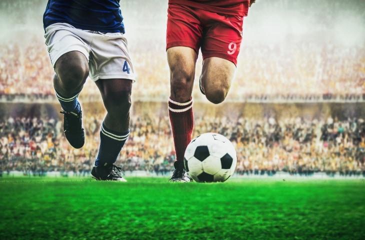 voetballers benen bal gras