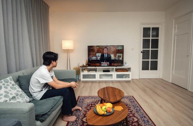 Jongen in woonkamer kijkt naar persconferentie Rutte